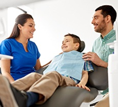 Father and young son speaking to dentist at appointment