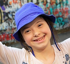 Smiling young girl wearing blue hat