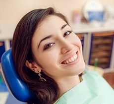 Smiling young woman in dental chair
