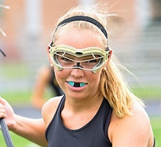 Teen girl playing lacrosse with green mouthguard