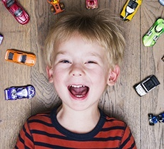 Laughing little boy surrounded by toy cars