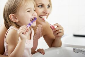 a mom and daughter brushing their teeth