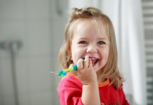 little girl smiling with toothbrush