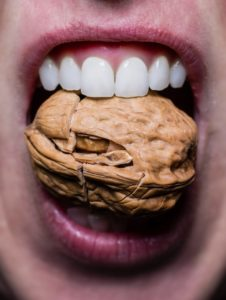 close up of mouth cracking a nut